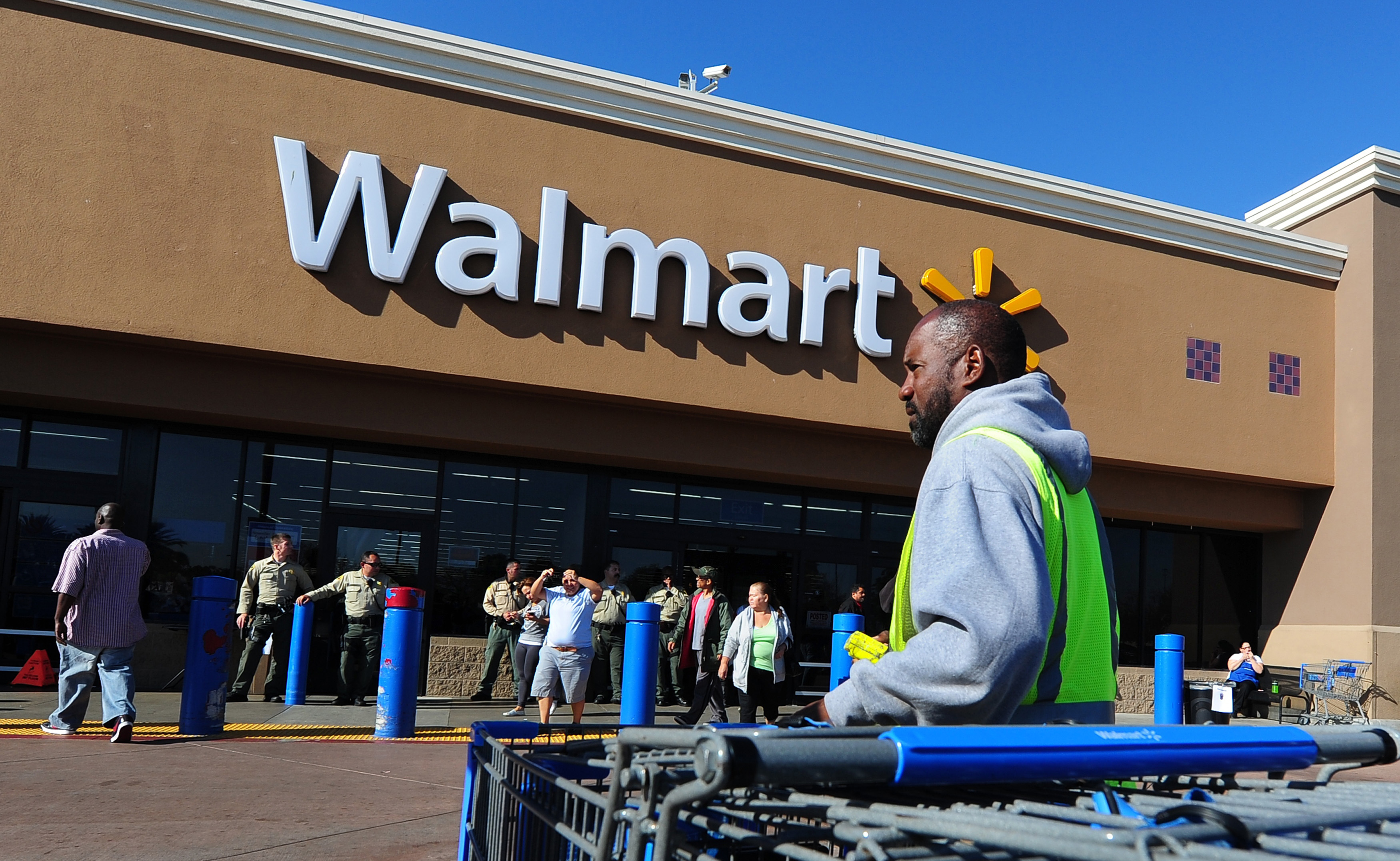 A Walmart employee gathers pushcarts as police man the front of a Walmart store amid heightened Black Friday security in Paramount, California on November 23, 2012 as Walmart employees and their supoorters protested nearby. The US retail giant Walmart admitted on November 27 some of its products were made at the Bangladesh garment factory that burnt down at the weekend killing 110 workers, as anger grows over lax safety standards. The fire broke out at the ground-floor warehouse of the multi-storey Tazreen Fashions factory 30 kilometres (18 miles) north of Dhaka on the night of November 24, trapping hundreds of workers on the upper upper floors, police said.  AFP PHOTO / Frederic J. BROWN        (Photo credit should read FREDERIC J. BROWN/AFP/Getty Images)